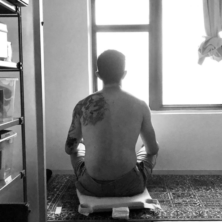 Back of man sitting, meditating, in front of a window